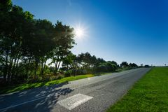 Empty asphalt country road passing through green fields and forests. Countryside landscape on sunny spring day in France Royalty Free Stock Images