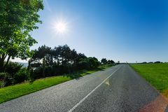 Empty asphalt country road passing through green fields and forests. Countryside landscape on sunny spring day in France Stock Image