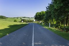 Empty asphalt country road passing through green fields and forests. Countryside landscape on sunny spring day in France Royalty Free Stock Photo