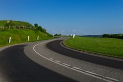 Empty asphalt curvy road passing through green fields. Countryside landscape on a bright sunny day in Normandy, France. Transport, industrial agriculture Royalty Free Stock Image