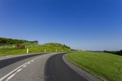 Empty asphalt curvy road passing through green fields. Countryside landscape on a bright sunny day in Normandy, France Royalty Free Stock Images
