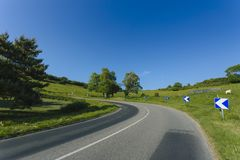 Empty asphalt curvy road passing through green fields. Countryside landscape on a bright sunny day in Normandy, France. Transport, industrial agriculture Royalty Free Stock Images