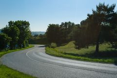 Empty asphalt curvy road passing through green fields and forests. Countryside landscape on a bright sunny day in Royalty Free Stock Image