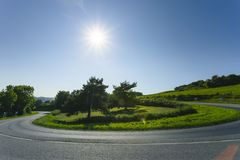 Empty asphalt curvy road passing through green fields and forests. Countryside landscape on a sunny spring day in France. Sunbeams in the sky. Transport Royalty Free Stock Photography