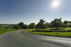 Empty asphalt curvy road passing through green fields and forests. Countryside landscape on a sunny spring day in France Stock Image