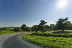 Empty asphalt curvy road passing through green fields and forests. Countryside landscape on a sunny spring day in France Stock Photos