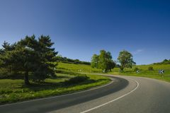 Empty asphalt curvy road passing through green fields and forests. Countryside landscape on a sunny spring day in France Royalty Free Stock Images