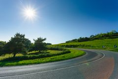 Empty asphalt curvy road passing through green fields and forests. Countryside landscape on a sunny spring day in France. Sunbeams in the sky. Transport Stock Photography