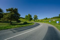 Empty asphalt curvy road passing through green fields and forests. Countryside landscape on a sunny spring day in France. Sunbeams in the sky. Transport Royalty Free Stock Image