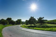 Empty asphalt curvy road passing through green fields and forests. Countryside landscape on a sunny spring day in France Stock Photography