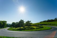 Empty asphalt curvy road passing through green fields and forests. Countryside landscape on a sunny spring day in France. Sunbeams in the sky. Transport Stock Image