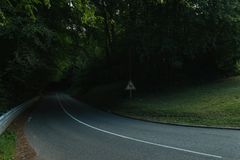 Empty asphalt curvy road passing through the green forest in the region of Normandy, France. Nature in summer. Countryside landscape, transportation and road Royalty Free Stock Photos