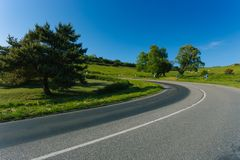 Empty Asphalt Curvy Road Passing Through Green Fields And Forests. Countryside Landscape On A Bright Sunny Day In Royalty Free Stock Images