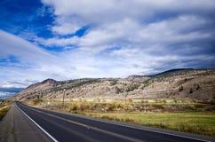 Empty asphalt highway through mountainous country. Empty asphalt highway receding into the distance through mountainous countryside under a cloudy blue sky royalty free stock photos