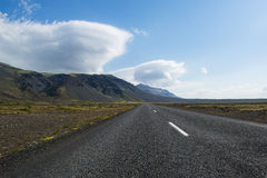 Empty asphalt Icelandic road surrounded by mountains and lenticular clouds Stock Photos
