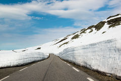Empty asphalt mountain road with high snow level at July, Norway Stock Photos