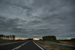 Empty asphalt road in bend on overcast spring day. With light at the horizon, in Lithuania Stock Photo