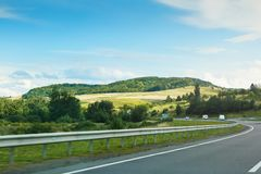 The empty asphalt road and blue sky with white clouds on the sunny day. Classic panorama view of road through fields. And hills royalty free stock image