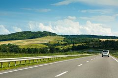The empty asphalt road and blue sky with white clouds on the sunny day. Classic panorama view of road through fields. And hills royalty free stock photos