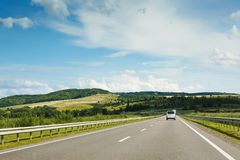 The empty asphalt road and blue sky with white clouds on the sunny day. Classic panorama view of road through fields. And hills royalty free stock photography
