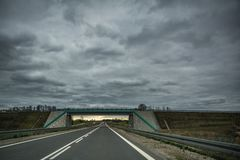 Empty asphalt road and a bridge on overcast summer day. In Lithuania Royalty Free Stock Photos