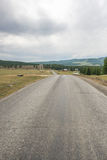 Empty asphalt road leading to mountains.  Stock Images