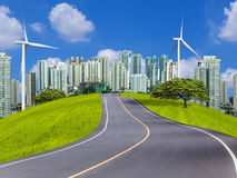 Empty asphalt road and modern city with wind turbines Royalty Free Stock Photography
