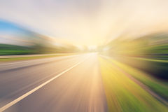 Empty asphalt road in motion blur and sunlight Royalty Free Stock Image