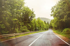 Empty asphalt road in mountains, tinted photo with some filters.  Royalty Free Stock Photography