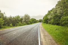 Empty asphalt road in mountains, tinted photo with some filters.  Stock Images