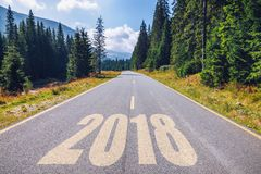 Empty asphalt road and New year 2018 concept. Driving on an empt. Y road in the mountains to upcoming 2018 and leaving behind old 2017. Concept for success and Stock Photography