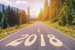 Empty asphalt road and New year 2018 concept. Driving on an empt. Y road in the mountains to upcoming 2018 and leaving behind old 2017. Concept for success and Stock Image
