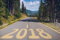 Empty asphalt road and New year 2018 concept. Driving on an empt. Y road in the mountains to upcoming 2018 and leaving behind old 2017. Concept for success and Royalty Free Stock Image