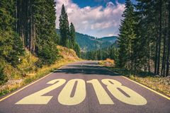 Empty asphalt road and New year 2018 concept. Driving on an empt. Y road in the mountains to upcoming 2018 and leaving behind old 2017. Concept for success and Royalty Free Stock Photo