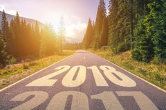 Empty asphalt road and New year 2018 concept. Driving on an empt. Y road in the mountains to upcoming 2018 and leaving behind old 2017. Concept for success and Stock Images