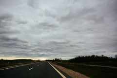 Empty asphalt road on overcast summer day in Lithuania. Cinematic filter applied with grain Stock Photography