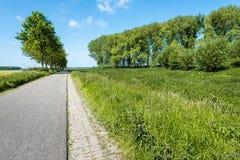 Empty asphalt road through a rural area in the spring season Stock Image