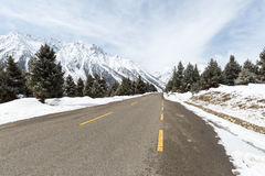 Empty asphalt road between the snow mountain Royalty Free Stock Images