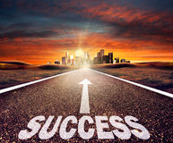 Empty asphalt road with success sign towards a city Stock Images