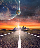 Empty asphalt road towards a city with planet background. Royalty Free Stock Image