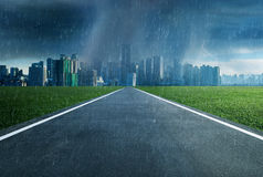 Empty asphalt road towards a city in storm Stock Photography