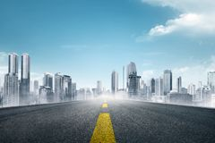 Empty asphalt road towards modern city. With skyscrapers building Royalty Free Stock Photography