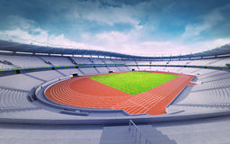 Empty athletics stadium with track and grass field at corner view Stock Image