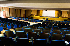 Empty auditorium with blue chairs and silver screen from above