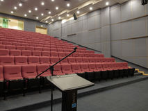 Empty Auditorium with Podium/Rostrum. Empty auditorium with sound-proofing. Red chairs with black rostrum/podium Royalty Free Stock Images
