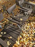 Autumn Yellow leaves covered Park ground and benches Royalty Free Stock Images