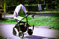 Empty baby stroller in garden Royalty Free Stock Photos