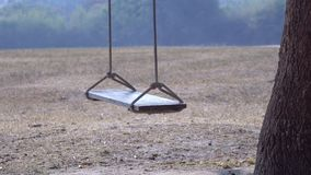 Empty baby swing on the tree stock video footage