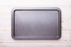 Empty baking tray on white wooden desk. Close up top view horizontally royalty free stock photo
