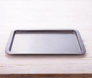 Empty baking tray on white wooden desk Royalty Free Stock Photos